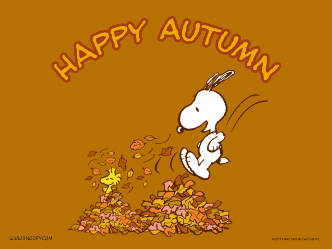 snoopy jumping in a pile of leaves